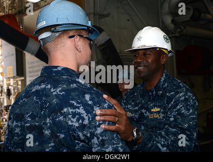 Commander of Expeditionary Strike Group (ESG) 3 Rear Adm. Frank Pond thanks Seaman David Rosser for his service - Stock Photo