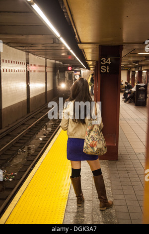 Young woman waiting for the F train at the 34th Street Station in NYC. - Stock Photo