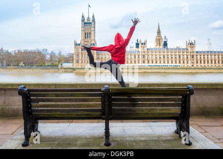 Young male dancer mid air in front of parliament, London, UK - Stock Photo