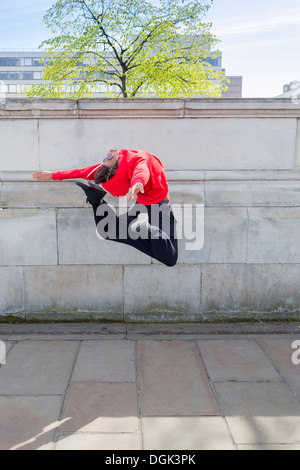 Young male dancer mid air in city - Stock Photo