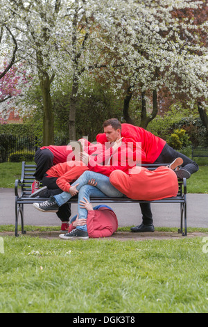 Group of young people performing on city park bench - Stock Photo