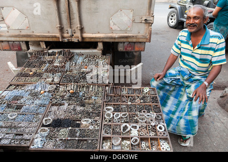 Man selling nuts and bolts in the Indian Market in Yangon in Myanmar. - Stock Photo