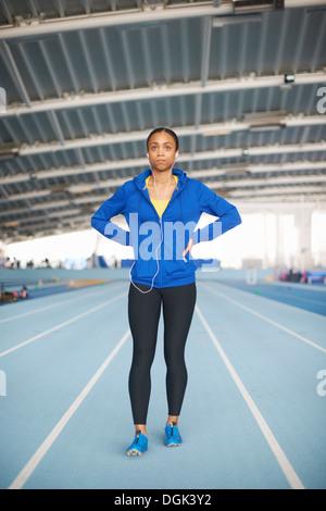 Young female athlete wearing earphones - Stock Photo