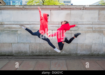 Young male and female dancer mid air in city - Stock Photo