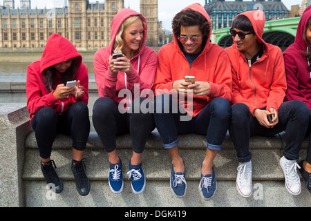 Group of young people looking at mobile phone - Stock Photo
