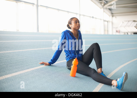 Young female athlete wearing earphones resting - Stock Photo