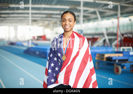 Young female athlete wrapped in US flag with gold medal - Stock Photo