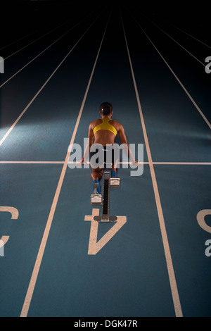Young female athlete on starting blocks, high angle - Stock Photo