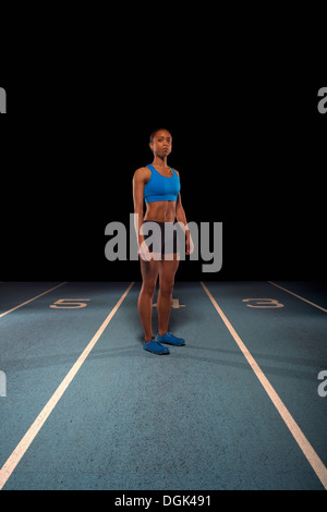 Young female athlete standing on race track - Stock Photo