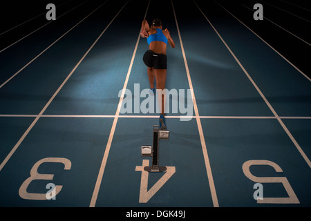 Young female athlete starting race, high angle - Stock Photo