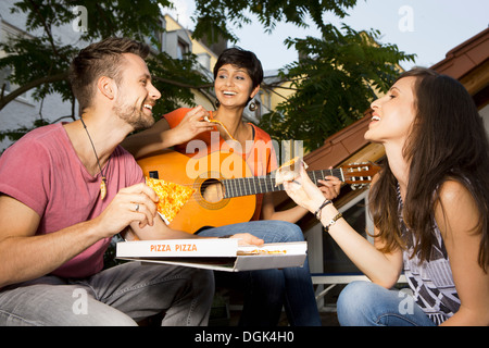 Three friends eating pizza, woman playing guitar - Stock Photo