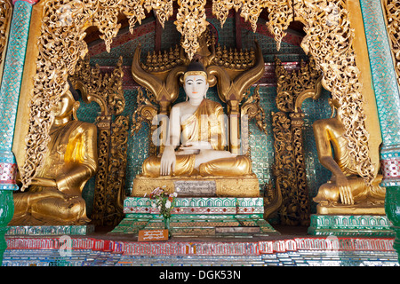 Ornate Buddhas at the Shwedagon Temple Complex in Yangon in Myanmar. - Stock Photo
