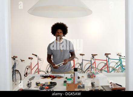 Mature man working in bicycle repair shop - Stock Photo