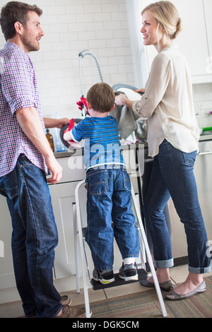 Parents and son washing dishes - Stock Photo