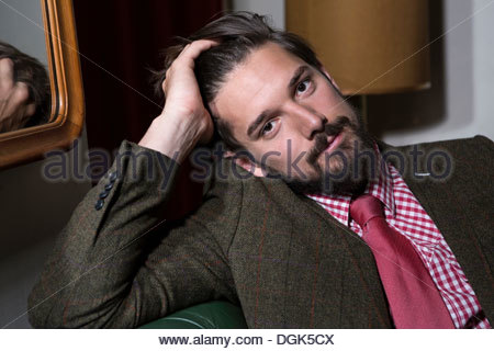 Portrait of man with hands in hair - Stock Photo