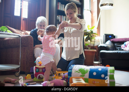 Mother helping daughter learn to walk - Stock Photo