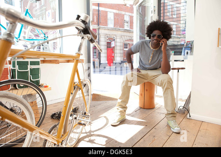 Mature man on cell phone in bicycle shop - Stock Photo