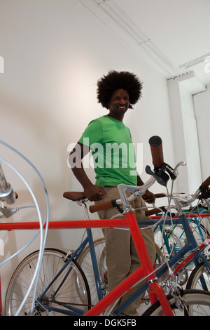 Mature man with bikes in bicycle shop - Stock Photo