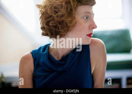 Close up profile of woman in sitting room - Stock Photo