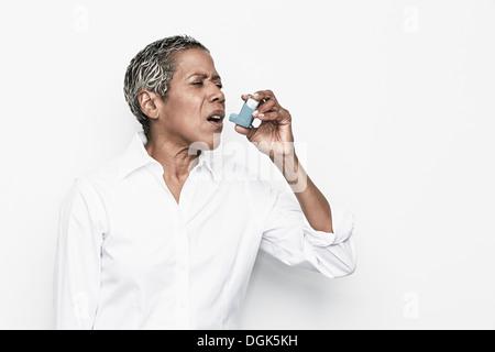 Senior woman using asthma inhaler - Stock Photo