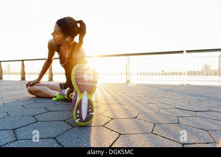 Young female jogger doing stretching exercise at sunrise - Stock Photo