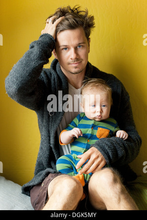 Tired father holding baby boy - Stock Photo