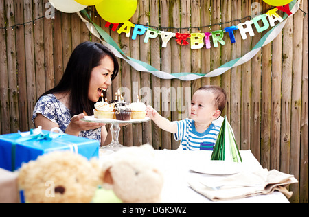 Mother showing cakes to baby boy - Stock Photo