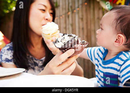 Mother and son feeding each-other cupcakes - Stock Photo