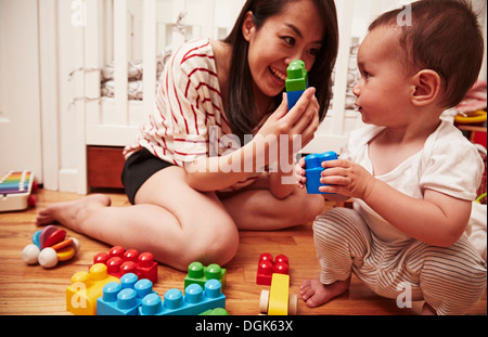 Mother and baby boy playing with building blocks - Stock Photo