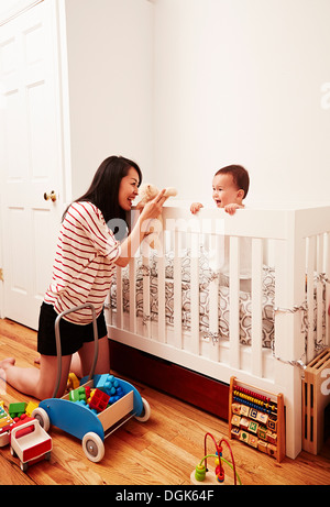 Mother playing with baby boy with soft toy - Stock Photo