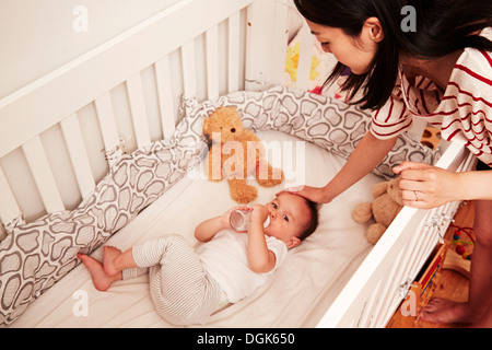 Baby boy lying in crib drinking baby bottle - Stock Photo