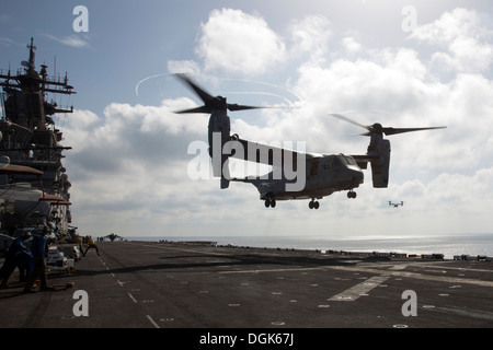 An MV-22 Osprey from Marine Medium Tiltrotor Squadron (VMM) 266 (Reinforced) lands on the flight deck of the amphibious - Stock Photo