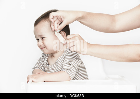 Hands applying plaster to baby's face - Stock Photo