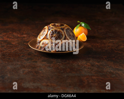 Christmas pudding decorated with sliced oranges - Stock Photo