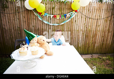 Baby boy sitting at table with soft toys wearing party hat - Stock Photo