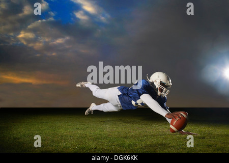 American football player reaching for touch down - Stock Photo