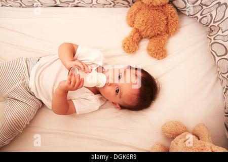 Baby boy lying in crib drinking baby bottle