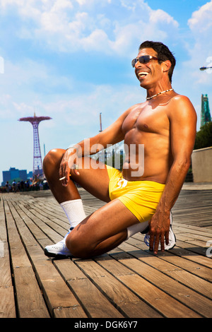 Portrait of man kneeling in yellow trunks, Brooklyn, New York, USA - Stock Photo