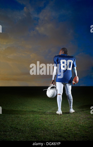 Rear view of American football player holding helmet - Stock Photo