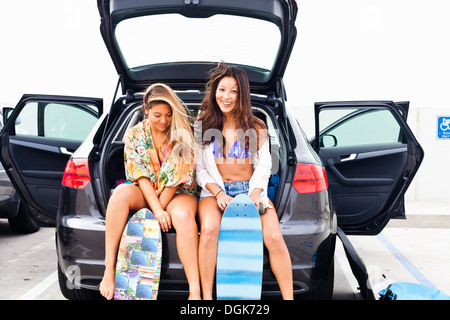 Female friends sitting in car boot with skateboards - Stock Photo
