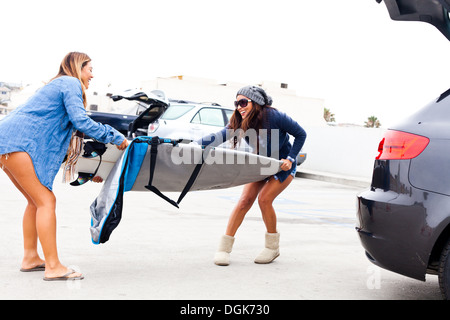 Female friends pulling cover from surfboard - Stock Photo