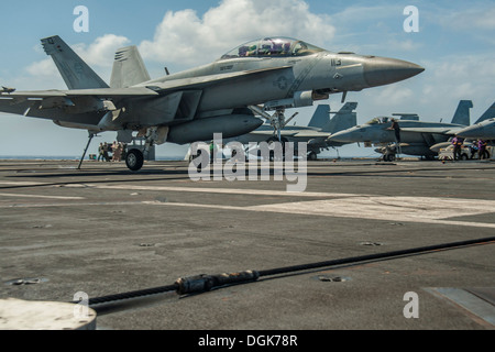 A F/A-18F Super Hornet from the Diamondbacks of Strike Fighter Squadron (VFA) 102 makes an arrested landing on the - Stock Photo