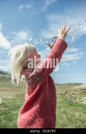 Young girl reaching to catch bubbles - Stock Photo