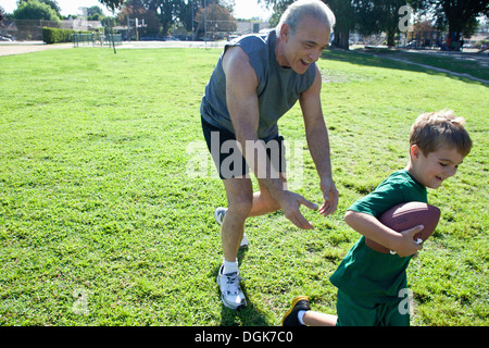Boy and grandfather playing american football - Stock Photo