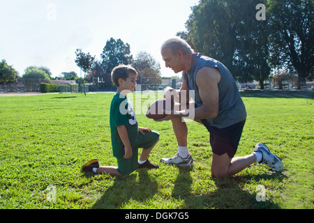 Boy and grandfather with american football - Stock Photo