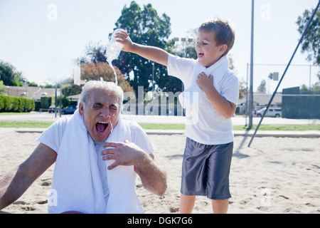 Boy pouring water on grandfather - Stock Photo
