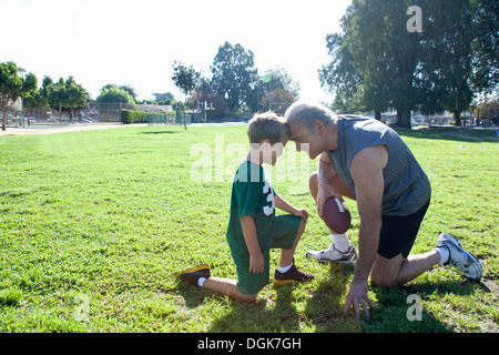 Boy and grandfather head to head, man holding football - Stock Photo