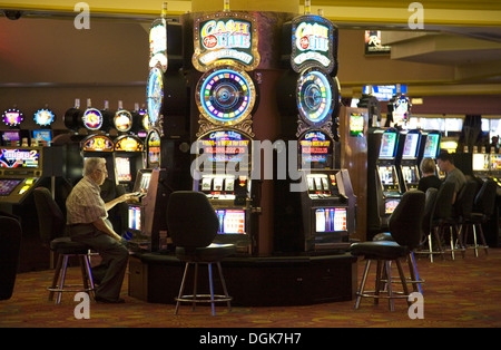 A man plays the slot machines at the Stratosphere hotel and casino in Las Vegas. - Stock Photo
