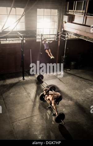 Two young adults working out in gym - Stock Photo