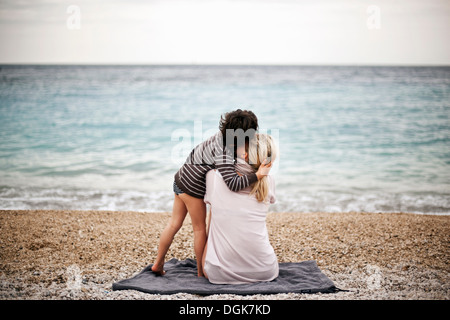 Boy hugging mother on a beach, rear view - Stock Photo